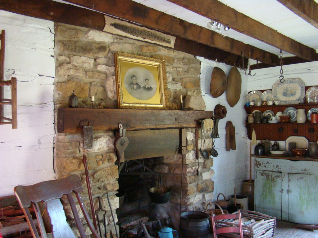 A view of the fireplace in Dietrich Cabin. Jacob and Catherine Dietrich's wedding photo is displayed on the mantel.