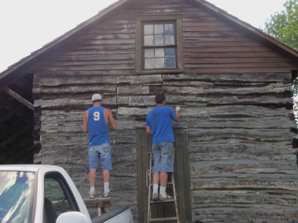 The Wilsons apply new chinking to the cabin walls.