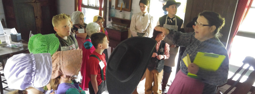 Children learning about 19th Century clothing during Pioneer Days Summer Day Camp.