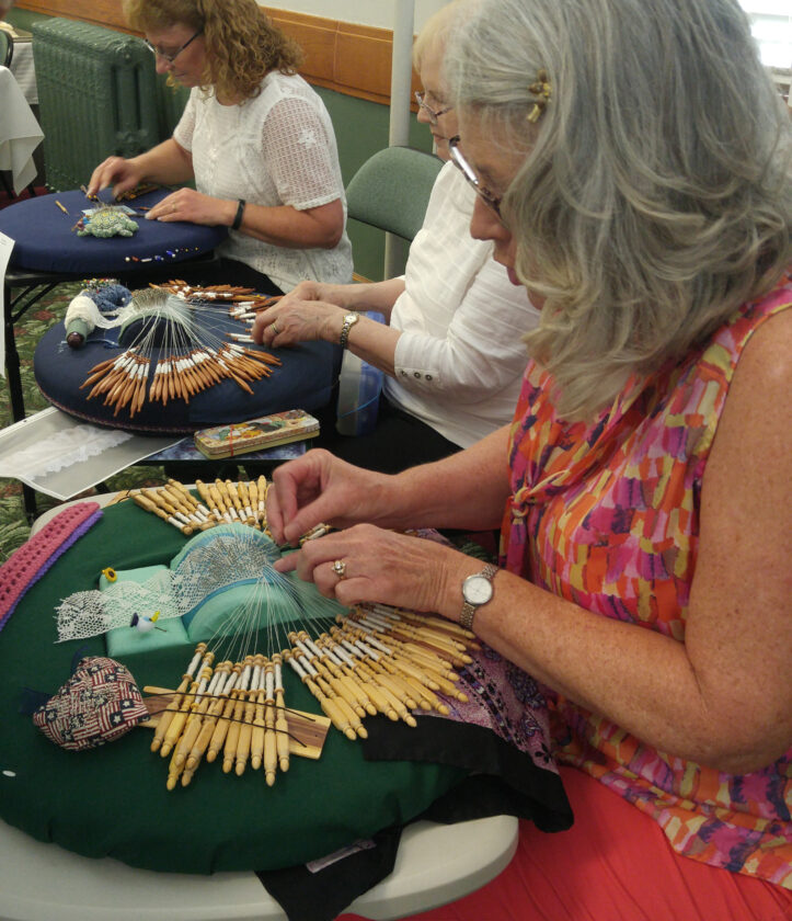 Three women sit in front of tables covered in lacemaking equipment.