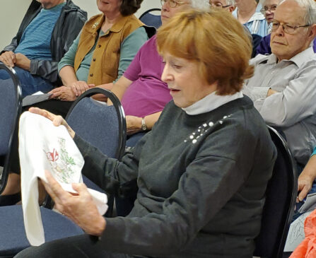 A woman sitting in a crowd holds a white linen embroidered pillowcase.