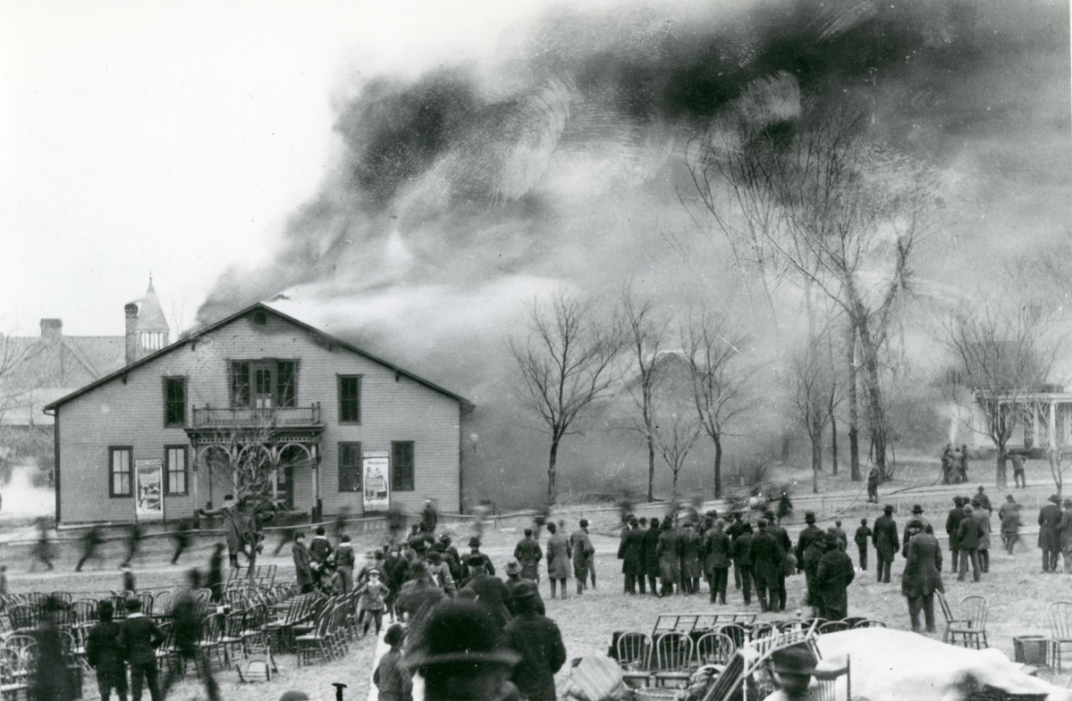 Exterior image of a theater building on fire. It is surrounded by onlookers and furniture removed from the burning building. A group of people are running with a fire hose. Smoke billows out of the building.